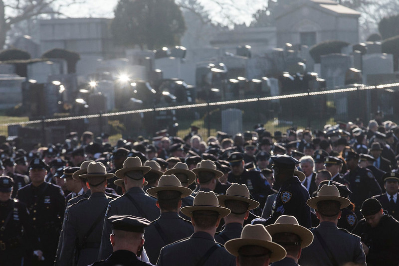 . Law enforcement personnel begin to gather for the funeral of New York city police officer Rafael Ramos in the Glendale section of Queens, Saturday, Dec. 27, 2014, in New York. Ramos and his partner, officer Wenjian Liu, were killed Dec. 20 as they sat in their patrol car on a Brooklyn street. The shooter, Ismaaiyl Brinsley, later killed himself. (AP Photo/John Minchillo)