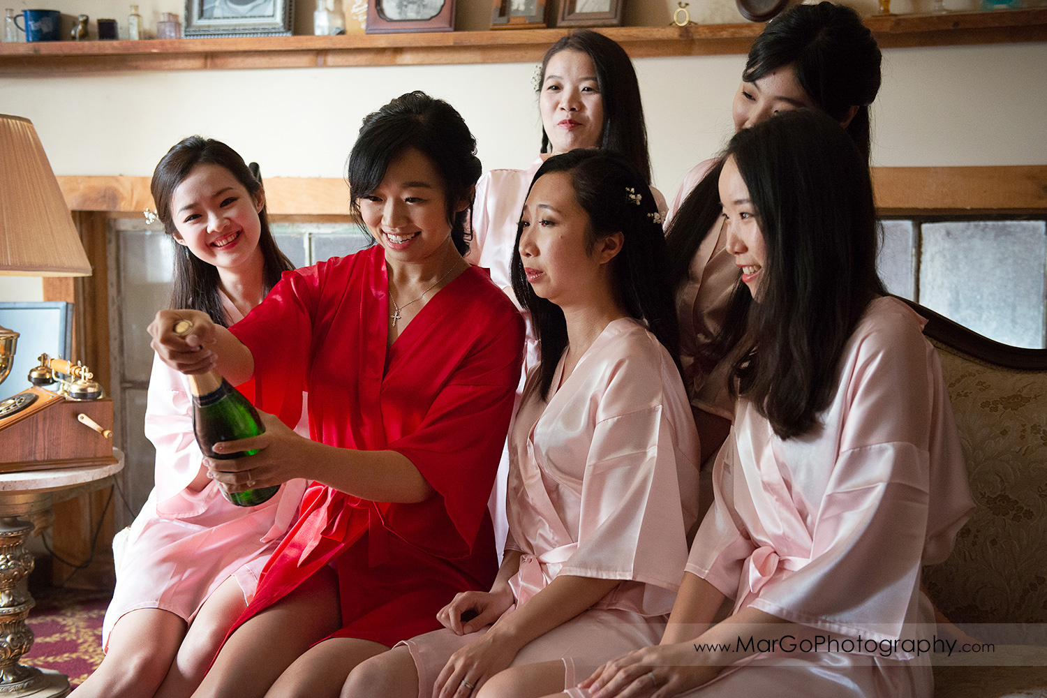 bride in red robe opening champagne with bridesmaids in pink robes at Long Branch Saloon & Farms in Half Moon Bay