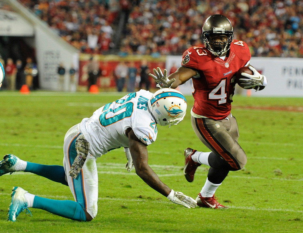 . Tampa Bay Buccaneers running back Bobby Rainey, right, slips past Miami Dolphins free safety Reshad Jones, left, for a 1-yard touchdown in the fourth quarter of an NFL football game in Tampa, Fla., Monday, Nov. 11, 2013.(AP Photo/Brian Blanco)