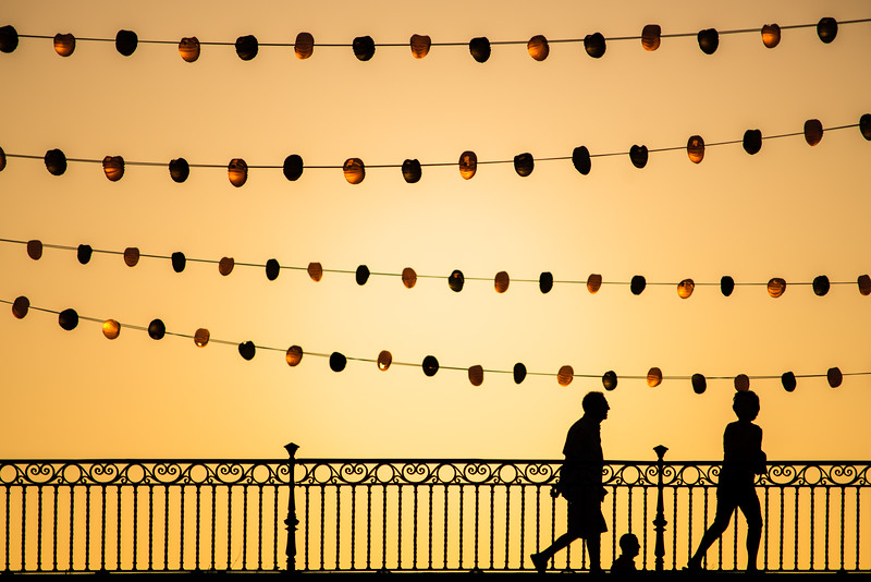 Pedestrians on Triana bridge during Vela de Santa Ana festival, Seville, Spain