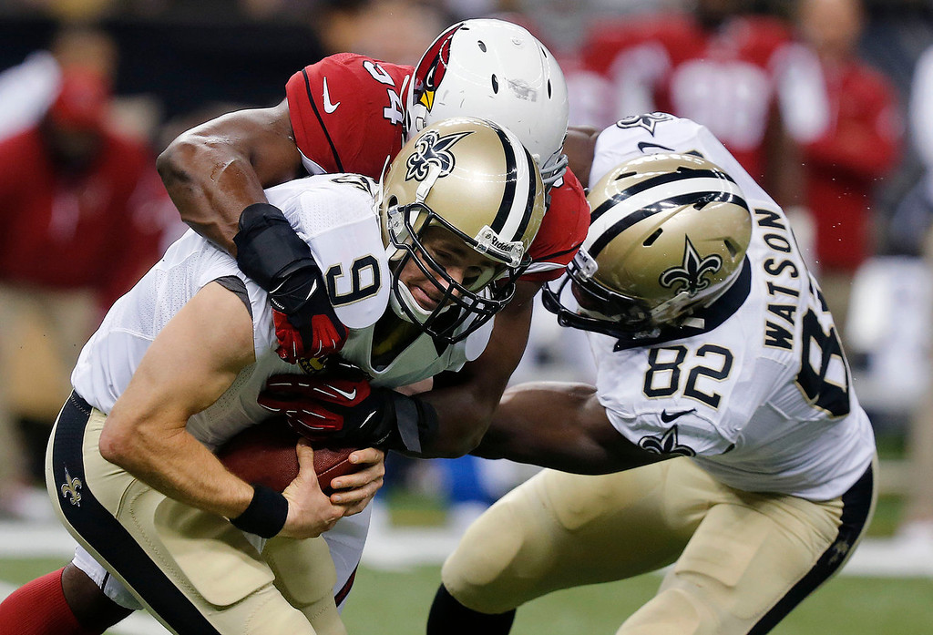 . New Orleans Saints quarterback Drew Brees (9) is sacked by Arizona Cardinals outside linebacker Sam Acho as Saints tight end Benjamin Watson (82) tries to block in the first half of an NFL football game in New Orleans, Sunday, Sept. 22, 2013. (AP Photo/Bill Haber)