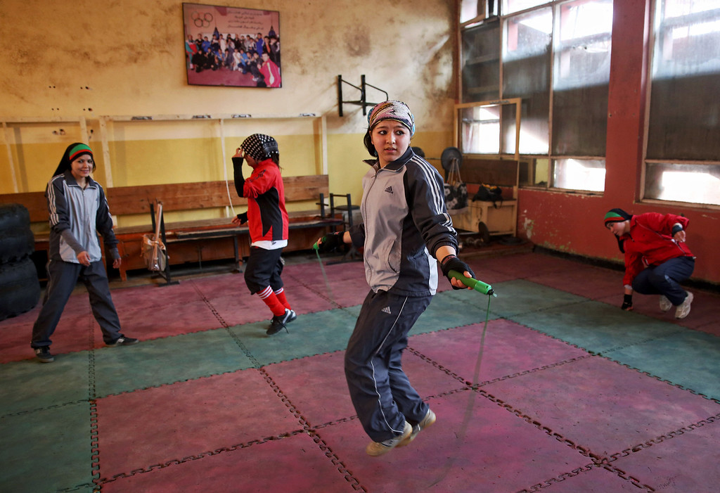. In this Wednesday, March, 5, 2014 photo, an Afghan female boxer, center, jumps rope during a practice session at the Kabul Stadium boxing club. The sportswomen share a camaraderie, laughing and teasing each other until the serious business of training begins. (AP Photo/Massoud Hossaini)
