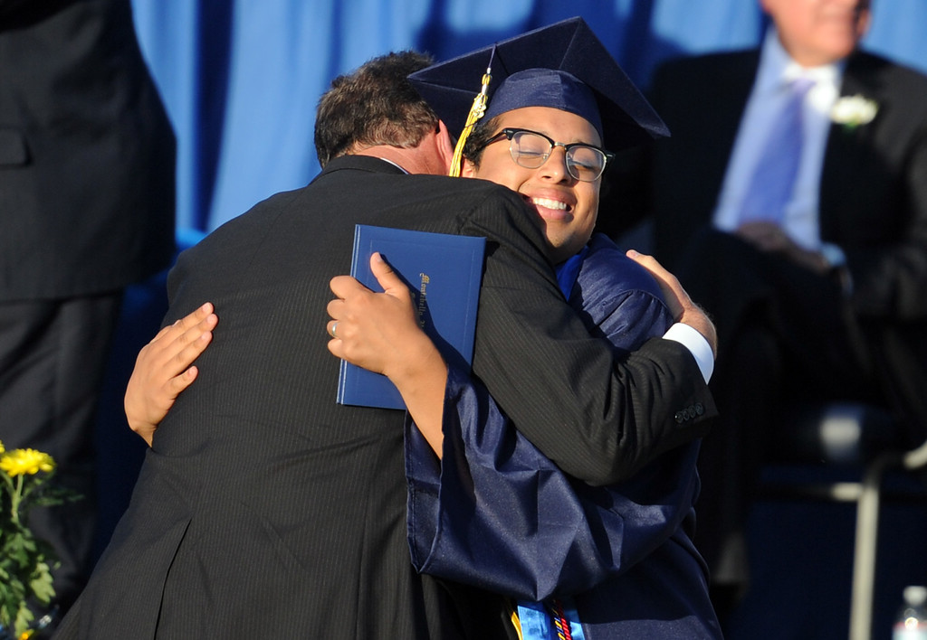 . Graduate Oscar Alvarado hugs principal Jeffrey Schwartz during the Montebello High School commencement at Montebello High School on Thursday, June 20, 2013 in Montebello, Calif.  (Keith Birmingham/Pasadena Star-News)