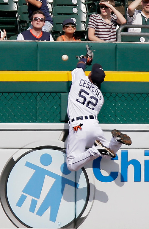 . Detroit Tigers left fielder Yoenis Cespedes goes up against the left field wall in an attempt to catch a home run hit by Cleveland Indians\' Brandon Moss during the ninth inning of a baseball game Sunday, June 14, 2015, in Detroit. The Tigers defeated the Indians 8-1. (AP Photo/Duane Burleson)