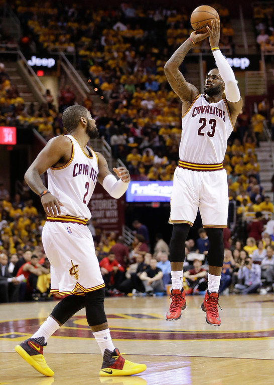 . Cleveland Cavaliers forward LeBron James puts up a 3-point shot as guard Kyrie Irving looks on in the second half against the Atlanta Hawks during Game 2 of the second round of the NBA playoffs on May 4 in Cleveland. James led the Cavs in points, with 27, and Irving led the Cavs in assists, with 6, in the team\'s 123-98 victory. Cleveland leads the series, 2-0. (AP Photo/Tony Dejak)
