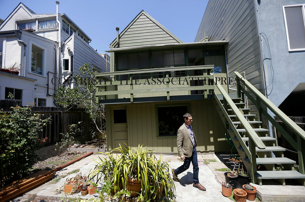 . George Limperis, a realtor with Paragon Real Estate Group, walks in the backyard of a property in the Noe Valley neighborhood in San Francisco, Wednesday, July 30, 2014. In the souped-up world of San Francisco real estate a $1 million will barely cover the cost of an 800-square-foot starter home that needs work and may or may not include private parking. (AP Photo/Jeff Chiu)