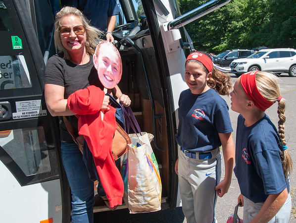 07/12/18 Wesley Bunnell | Staff Karolina Carlone, R, looks at her own cutout as mom Dorothy Carlone, stands near the the bus bringing the District 5 9-11 year old champions to their game on Thursday afternoon in Trumbull against Wilton. Teammate Jessica Petit is shown in the middle.