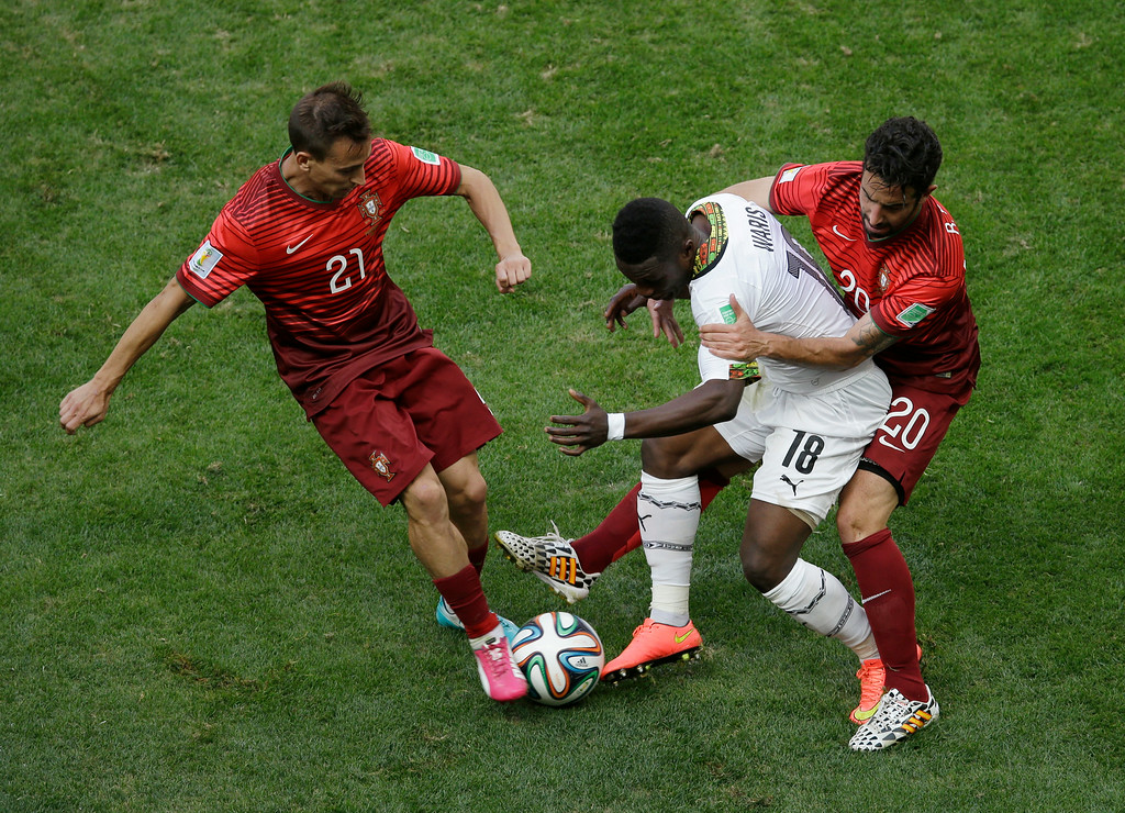 . Ghana\'s Majeed Waris, second from right, battles for the ball with Portugal\'s Joao Pereira, left, and Portugal\'s Ruben Amorim, right, during the group G World Cup soccer match between Portugal and Ghana at the Estadio Nacional in Brasilia, Brazil, Thursday, June 26, 2014. (AP Photo/Themba Hadebe)