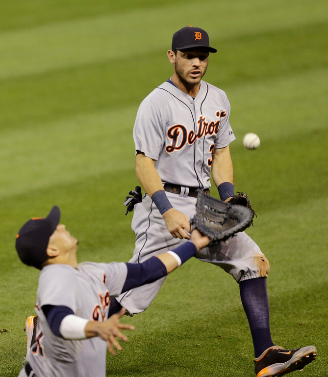 . Detroit Tigers\' Ian Kinsler, right, watches as first baseman Victor Martinez cannot get to ball hit by Cleveland Indians\' Yan Gomes in the fourth inning of a baseball game, Wednesday, Sept. 3, 2014, in Cleveland. Gomes was safe at first base and Lonnie Chisenhall scored on the play. (AP Photo/Tony Dejak)