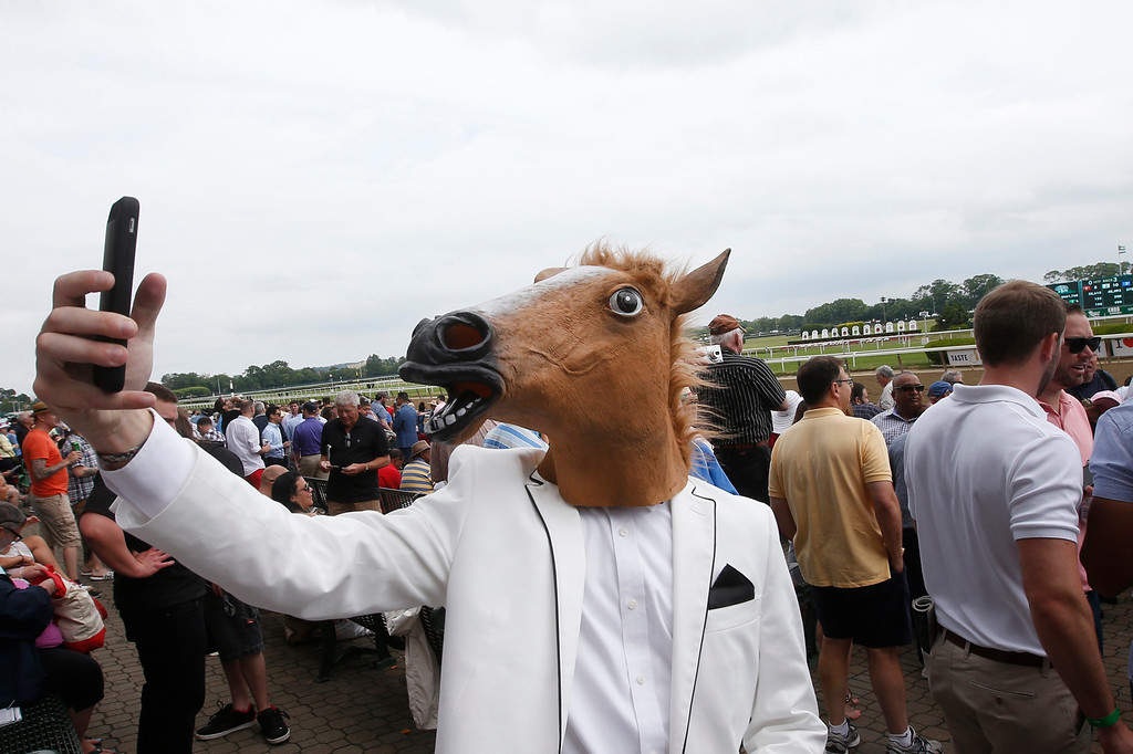 . A spectator wearing a horse mask takes a selfie before the 147th running of the Belmont Stakes horse race at Belmont Park, Saturday, June 6, 2015, in Elmont, N.Y.  American Pharoah will try for a Triple Crown when he runs in Saturday\'s race. (AP Photo/Jason DeCrow)