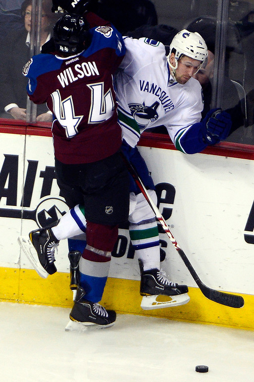 . DENVER, CO - MARCH 24: Ryan Wilson (44) of the Colorado Avalanche checks Keith Ballard (4) of the Vancouver Canucks during the second period of action. Colorado Avalanche versus the Vancouver Canucks at the Pepsi Center. (Photo by AAron Ontiveroz/The Denver Post)
