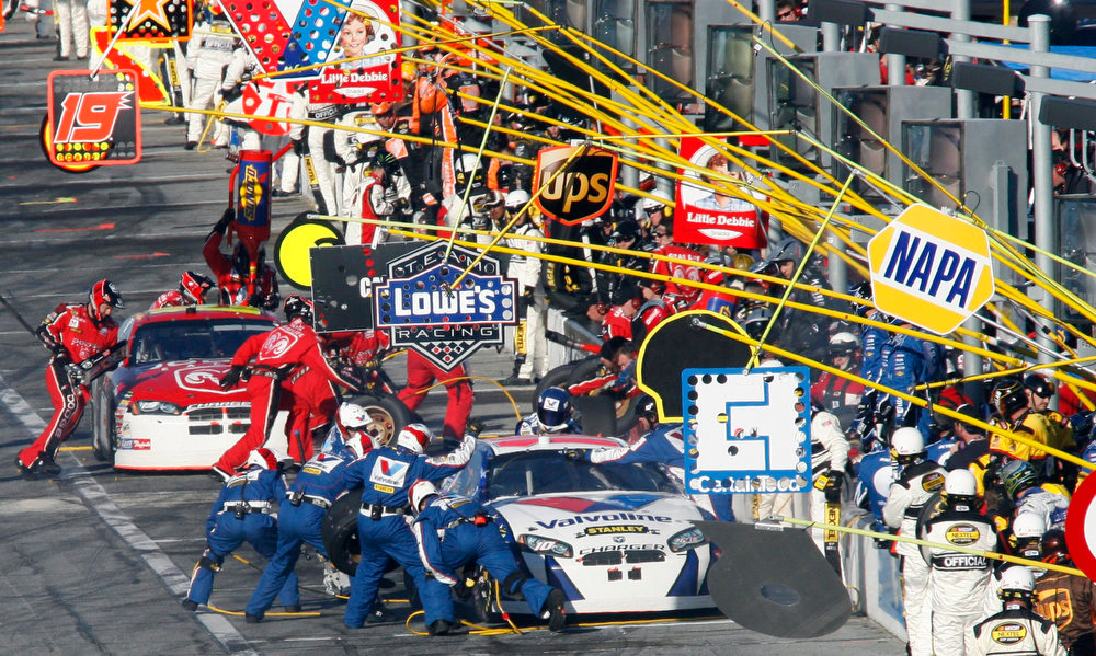 . Crews work on cars during pit stops in the NASCAR Daytona 500 auto race at Daytona International Speedway in Daytona Beach, Fla., Sunday, Feb. 18, 2007. Scott Riggs is at front. (AP Photo/Glenn Smith)