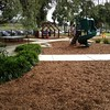 green plastic spiral slide and open plan cubby and aluminium seating pallet and native grass edging