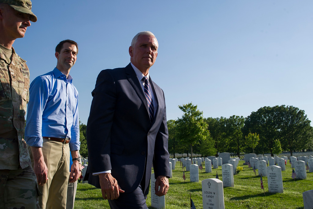 . Vice Mike Pence and Sen. Tom Cotton, R-Ark., walk through Section 60 after placing flags on the gravesites of fallen soldiers, while members of the Army 3d U.S. Infantry Regiment, The Old Guard, honor the nation\'s fallen military heroes during its annual Flags In ceremony at Arlington National Cemetery, Thursday, May 24, 2018, in Arlington, Va. (AP Photo/Cliff Owen)