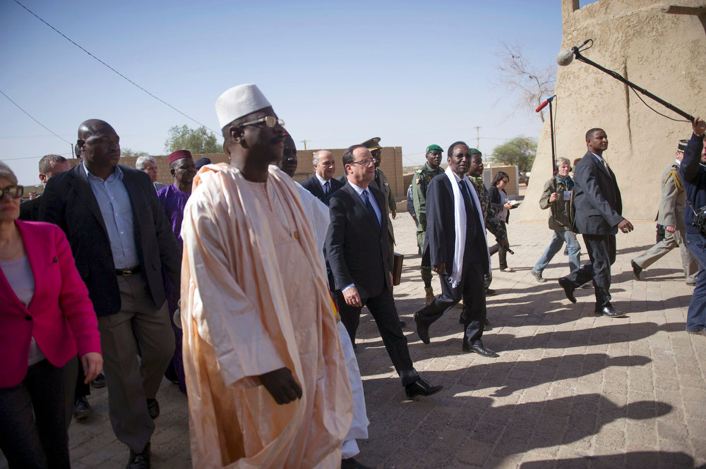 Description of . France\'s President Francois Hollande (C) flanked by Mali\'s interim president Dioncounda Traore (2ndR), and French Foreign Affairs minister Laurent Fabius (C Rear) arrive at the Djingareyber Mosque in Timbuktu during his one-day visit in Mali February 2, 2013.  President Hollande flew to Mali on Saturday to support French troops fighting Islamist rebels in the Sahel nation and he visited the famed ancient city of Timbuktu that was recaptured from al Qaeda-allied fighters six days ago. REUTERS/Fred Dufour/Pool