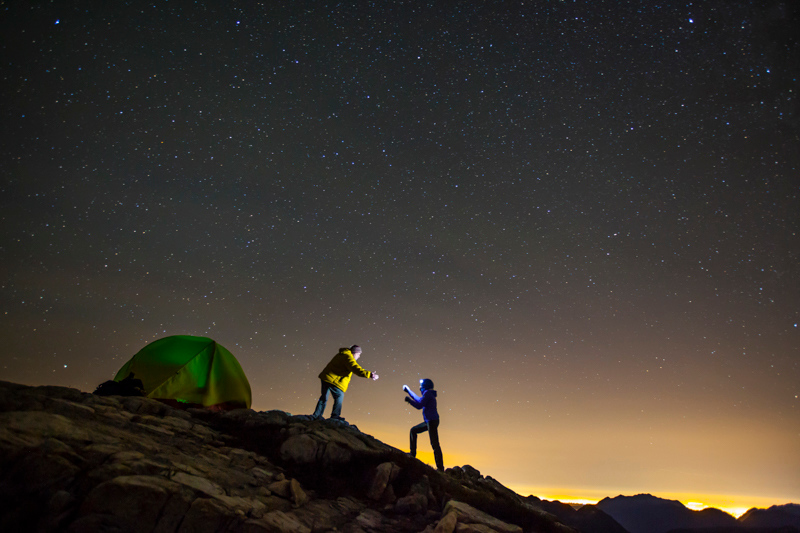 A backpacker holds out his hand to help his partner up a rocky slope towards their tent.