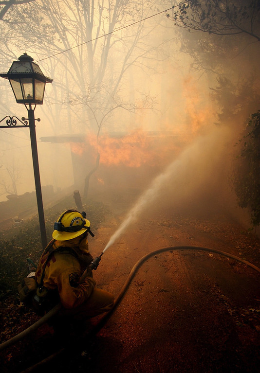 . Ten years ago this month the arson caused Old Fire, fanned by Santa Ana winds burned thousands of acres, destroyed hundreds of homes and caused six deaths. The fire burned homes in San Bernardino, Highland, Cedar Glen, Crestline, Running Springs and Lake Arrowhead and forced the evacuation of thousand of residents. A firefighter kneels down while spraying water on a house fire near Crestline, on Sunday October 26, 2003 on the second day of the Old Fire. (Staff file photo/The Sun)
