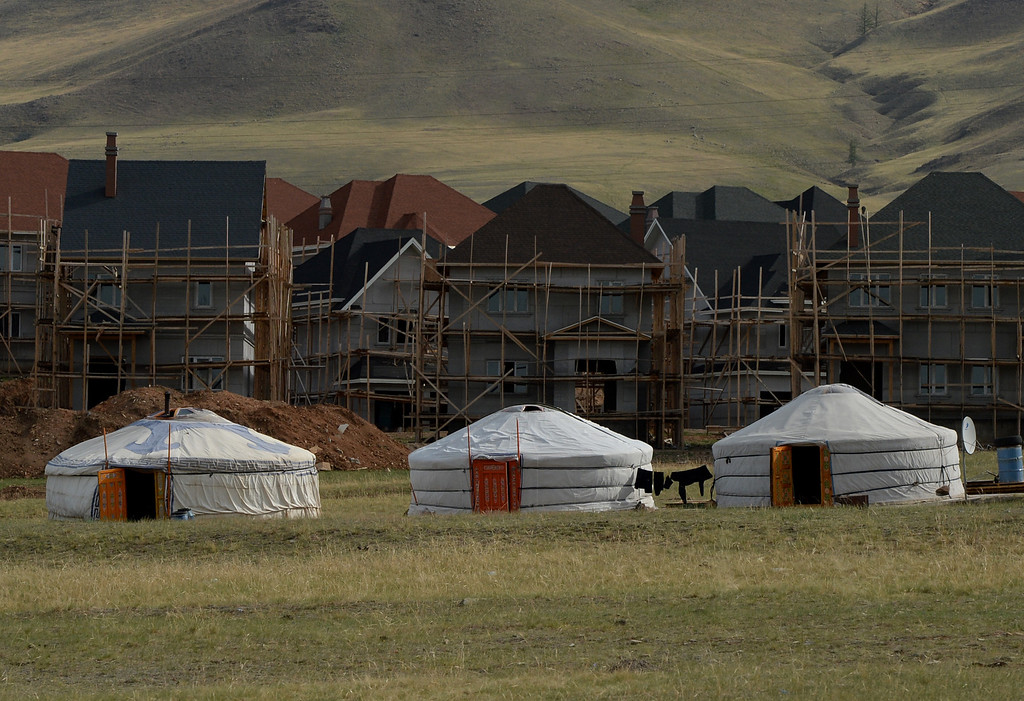 ". New housing under construction is pictured behind traditional Mongolian tents called a ""ger\"" or \""yurt\"" outside Ulan Bator on June 4, 2013. The country is in the middle of a resources boom with the huge copper and gold Oyu Tolgoi soon to open and which will provide vast revenues for the government that can be spent on infrastructure and education if corruption can be kept in check. MARK RALSTON/AFP/Getty Images"