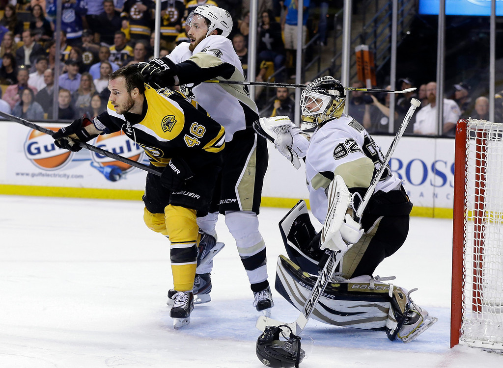 . Pittsburgh Penguins defenseman Brooks Orpik, center, checks Boston Bruins center David Krejci (46) as Penguins goalie Tomas Vokoun (92) guards the net during the second period in Game 3 of the Eastern Conference finals in the NHL hockey Stanley Cup playoffs, in Boston on Wednesday, June 5, 2013. (AP Photo/Elise Amendola)