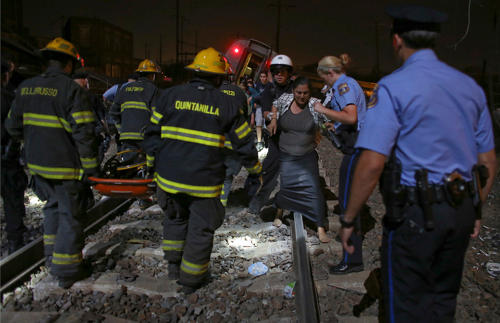 . Emergency personnel help passengers at the scene of a train wreck, Tuesday, May 12, 2015, in Philadelphia. An Amtrak train headed to New York City derailed and crashed in Philadelphia. (AP Photo/Joseph Kaczmarek)