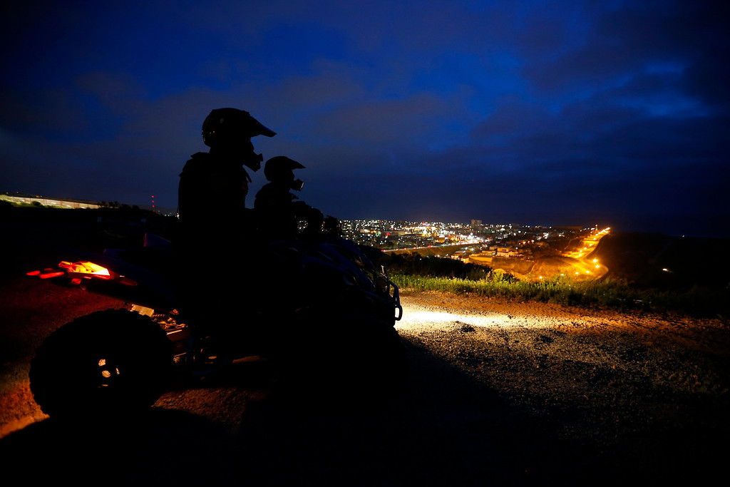 . U.S. Customs and Border Patrol agents sit on the ATVs atop a hill overlooking Tijuana, Mexico during their night patrol along the international border between Mexico and the United States, March 26, 2013. Picture taken March 26, 2013. REUTERS/Mike Blake