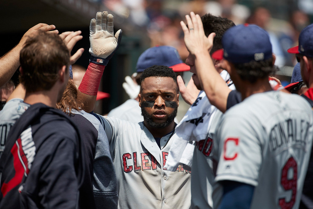 . Cleveland Indians\' Carlos Santana, center, is congratulated by teammates after scoring during the third inning against the Detroit Tigers in the first baseball game of a doubleheader in Detroit, Saturday, July 1, 2017. (AP Photo/Rick Osentoski)