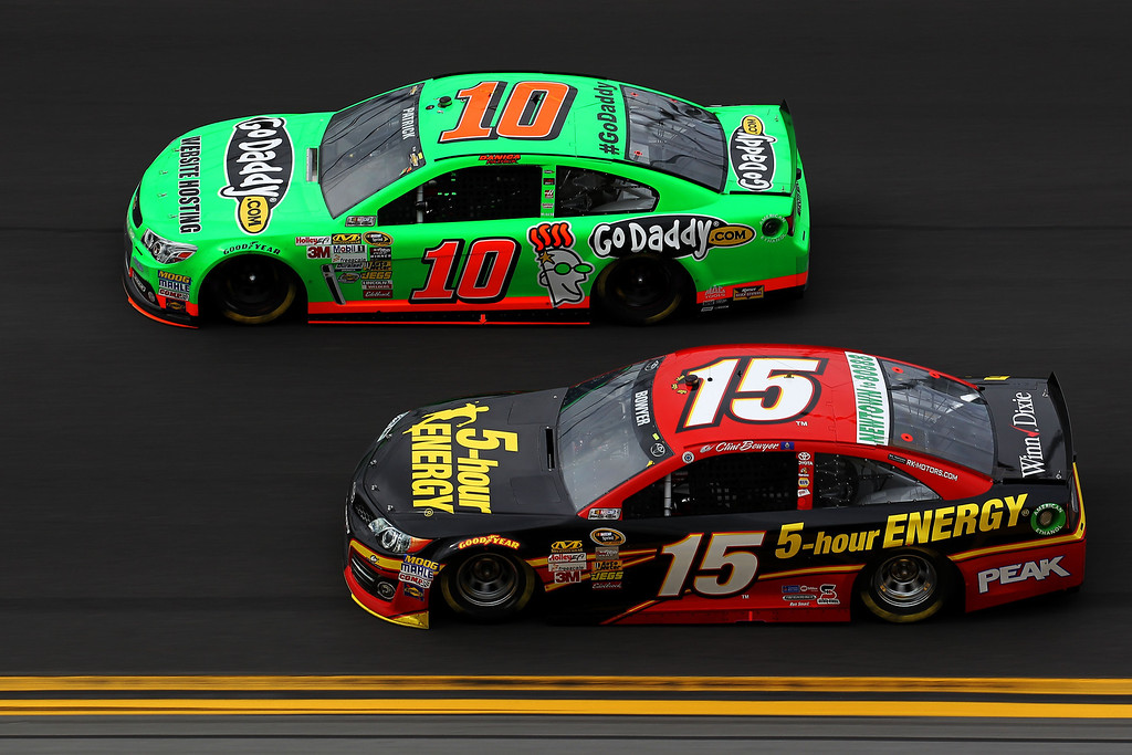 . Clint Bowyer, driver of the #15 5-hour ENERGY Toyota, and Danica Patrick, driver of the #10 GoDaddy.com Chevrolet, race during the NASCAR Sprint Cup Series Daytona 500 at Daytona International Speedway on February 24, 2013 in Daytona Beach, Florida.  (Photo by Todd Warshaw/Getty Images)