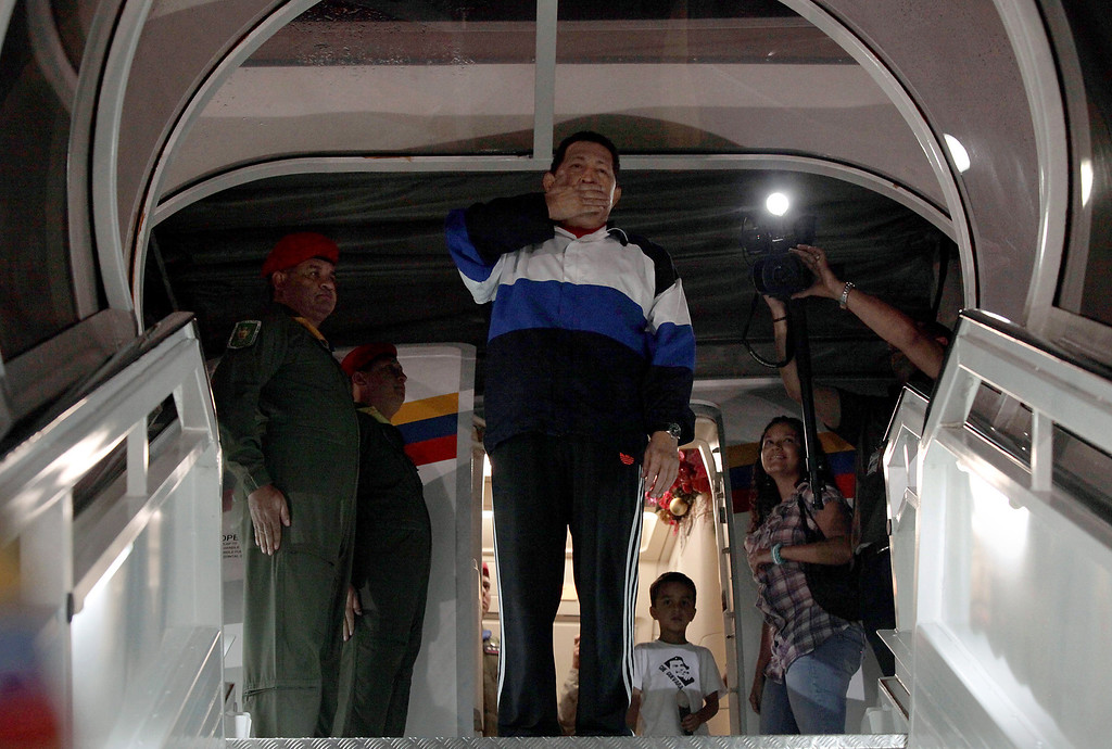. (FILE) Handout picture released by the Venezuelan Presidency showing Venezuela\'s President Hugo Chavez (C) blowing kisses from the plane stairs just before departing for Cuba to undergo new cancer surgery, on December 10, 2012 in Caracas. February 10, 2013 marks two months since Chavez\'s last public appearance, when he left for Cuba. Chavez underwent his fourth round of cancer surgery in Havana on December 11, and since then has neither been seen nor heard.   AFP PHOTO/PRESIDENCIA