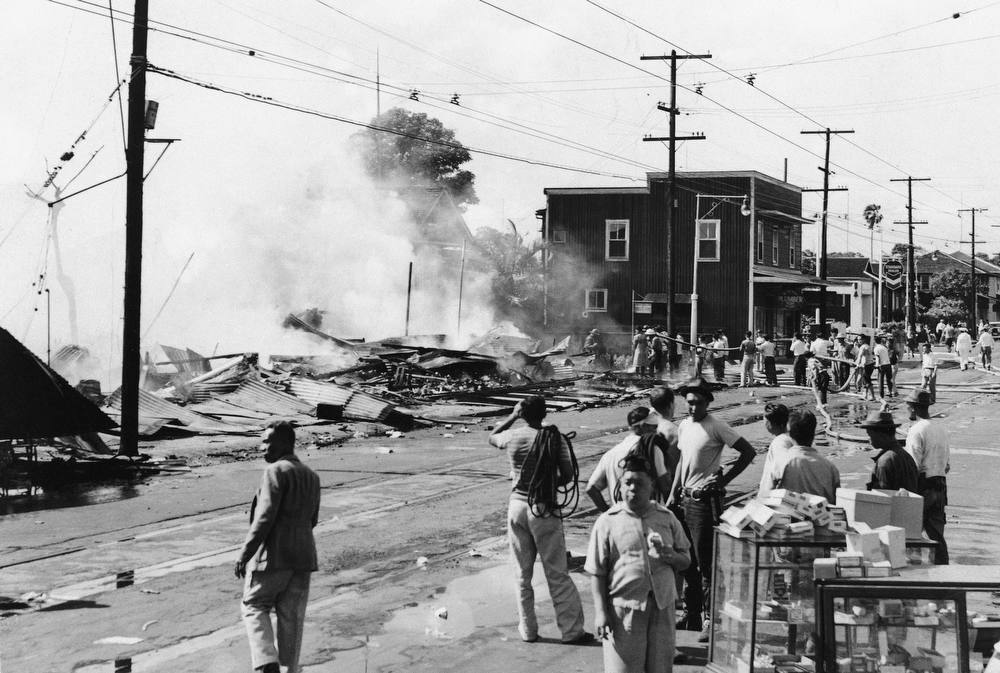 Description of . The wreckage of a drug store smolders at Waikiki after attack by Japanese planes, Dec. 7 1941. (AP Photo)