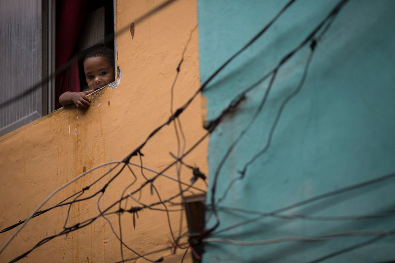 """. A young resident looks out from his window as military police officers patrol during an operation in the Mare slum complex, ahead of its \""""pacification,\"""" in Rio de Janeiro, Brazil, Tuesday, March 25, 2014. (AP Photo/Felipe Dana)"""