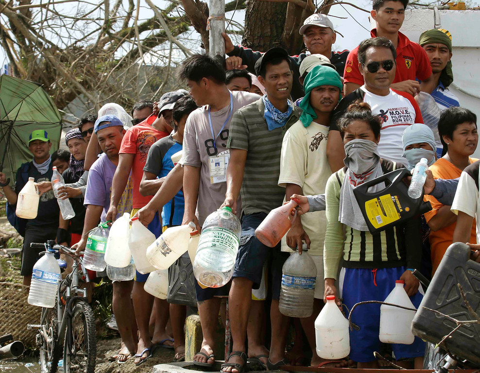 . Typhoon survivors line up to get fuel from an abandoned filling station Thursday, Nov. 14, 2013, in Tacloban city, Leyte province in central Philippines. Aid has been slow to reach the half-million people displaced by the storm that tore across several islands in eastern Philippines last Friday. (AP Photo/Bullit Marquez)