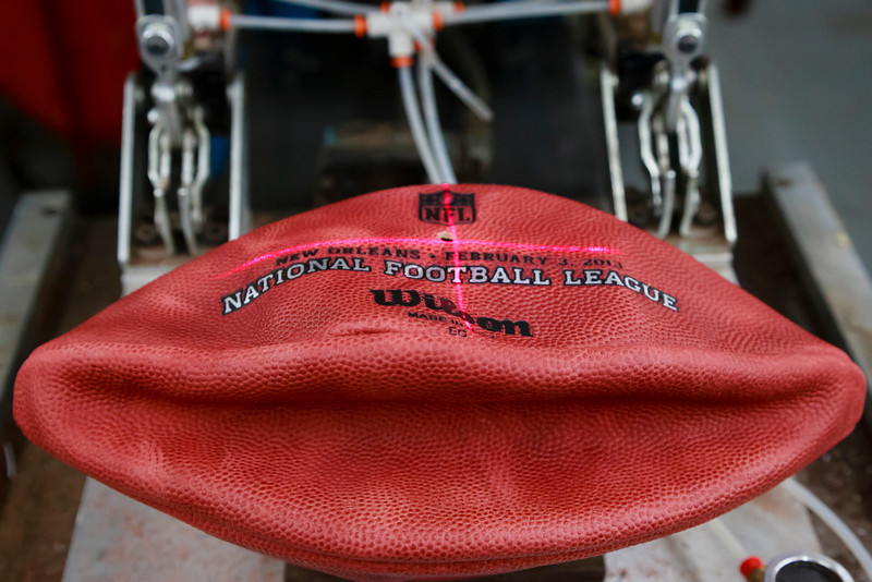 . A laser is used to lineup an official game ball for the NFL football Super Bowl XLVII so the team names can be branded onto it at Wilson Sporting Goods Co. in Ada, Ohio, Monday, Jan. 21, 2013.  (AP Photo/Rick Osentoski)