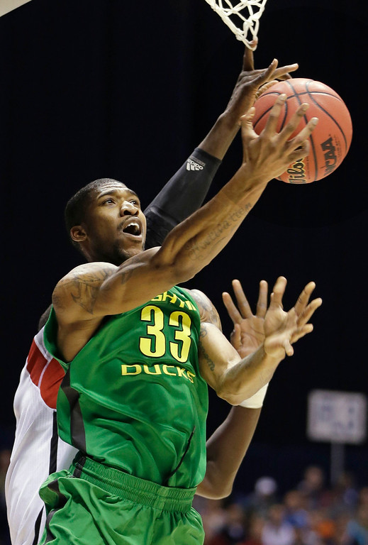 . Louisville center Gorgui Dieng blocks a shot from behind by Oregon forward Carlos Emory (33) during the first half of a regional semifinal in the NCAA college basketball tournament, Friday, March 29, 2013, in Indianapolis. (AP Photo/Darron Cummings)