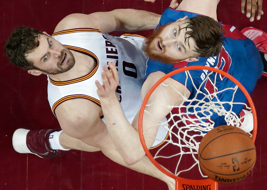 . Cleveland Cavaliers\' Kevin Love, left, drives to the basket against Detroit Pistons� Aron Baynes, from Australia, in the first half in Game 1 of a first-round NBA basketball playoff series, Sunday, April 17, 2016, in Cleveland. The Cavaliers won 106-101. (AP Photo/Tony Dejak)