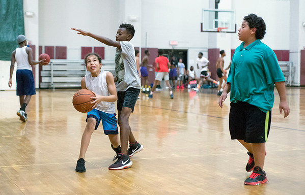 07/19/19 Wesley Bunnell | Staff Friends Frandy Almarzar, L, Zyhir Brown and Ezequiel Abru play a pick up basketball game on Friday July 19, 2019 at New Britain High School. Midnight Basketball, part of the NB PAL program, is holding basketball at NBHS every Friday from 6pm -12pm and Saturdays at Osgood Park under the supervision of a NB police officer.