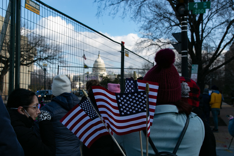 A masked group of people gathers near the U.S. Capitol amid a backdrop of National Guard troops and watch the inauguration live on their phones