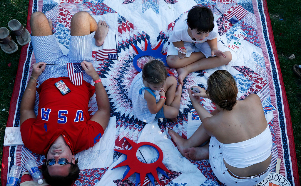 . The Walker family of Lafayette, La. relaxes while waiting for the start of the Boston Pops Fourth of July Concert at the Hatch Shell in Boston, Thursday, July 4, 2013. (AP Photo/Michael Dwyer)