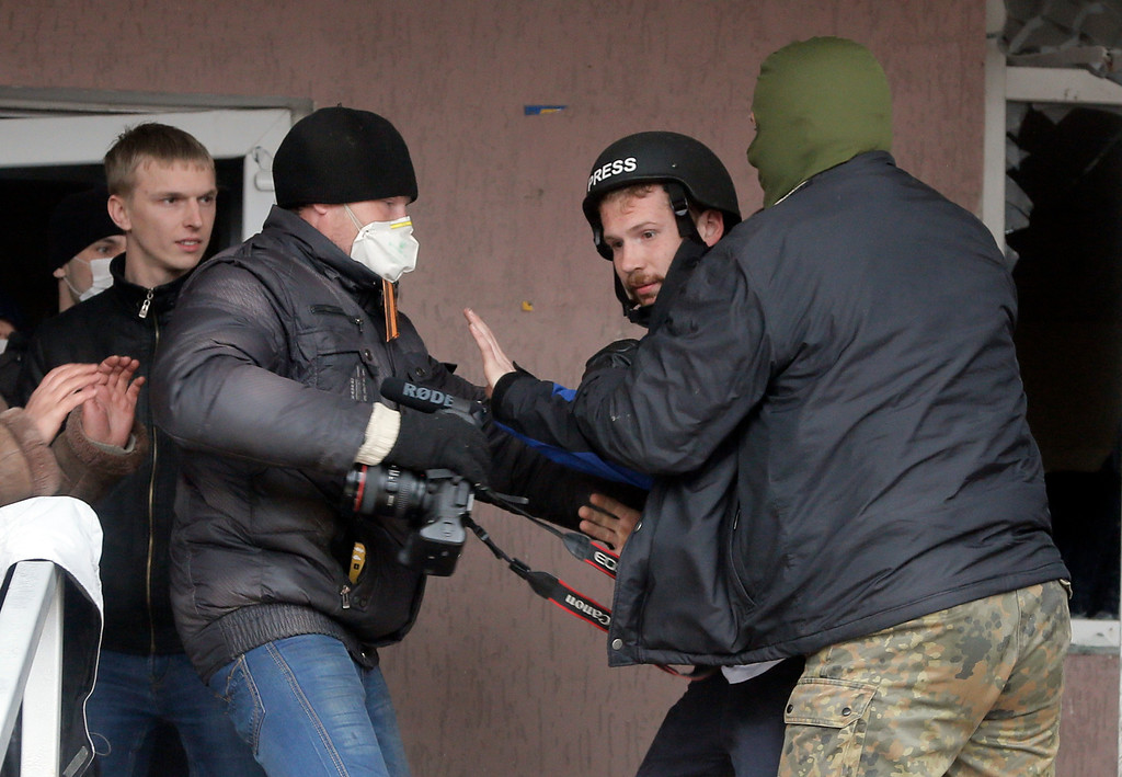 . Masked pro-Russian men attack British photojournalist Frederick Paxton, 2nd right, during the mass storming of a police station in the eastern Ukrainian town of Horlivka Monday, April 14, 2014.   (AP Photo/Efrem Lukatsky)