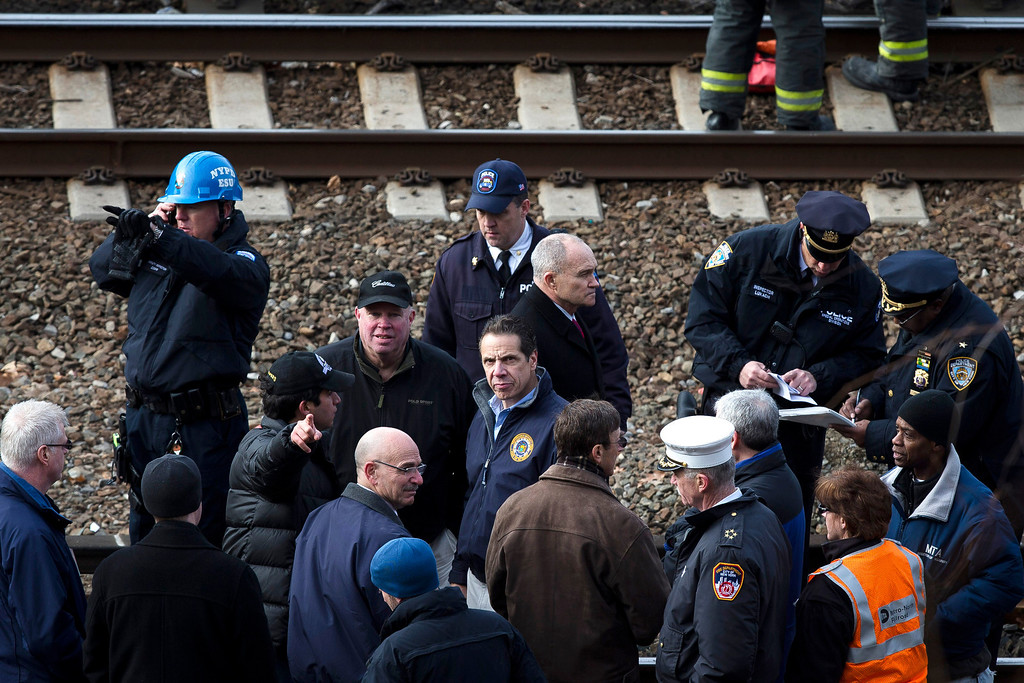 . New York Governor Andrew Coumo, center, NYPD Police Commissioner Ray Kelly, center right, and MTA Chairman and CEO Thomas Prendergast, center left, stand by the tracks at the scene of a Metro-North passenger train derailment in the Bronx borough of New York, Sunday, Dec. 1, 2013. The train derailed on a curved section of track in the Bronx on Sunday morning, coming to rest just inches from the water and causing multiple fatalities and dozens of injuries, authorities said. (AP Photo/John Minchillo)