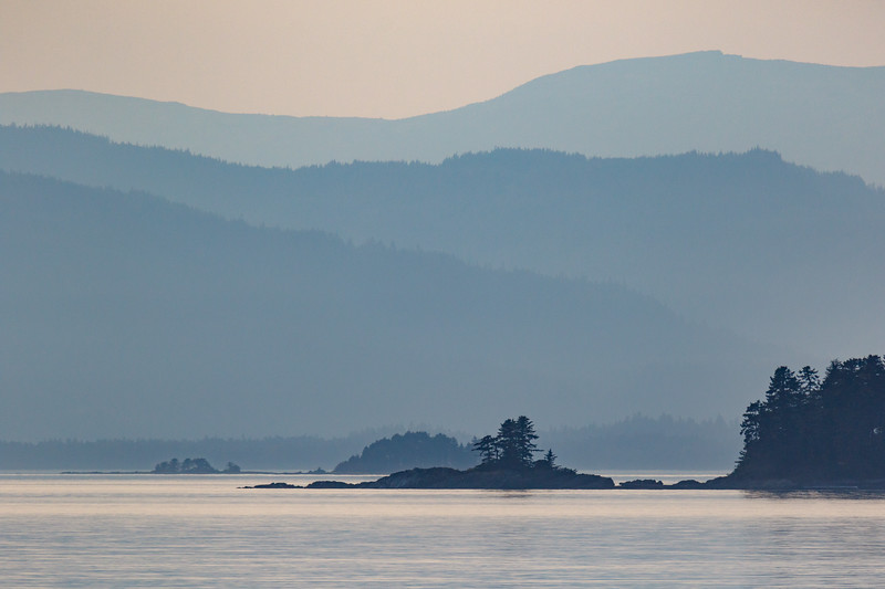 Layers of soft mountain silhouettes raise from calm and soothing blue sea in Alaska near sunset