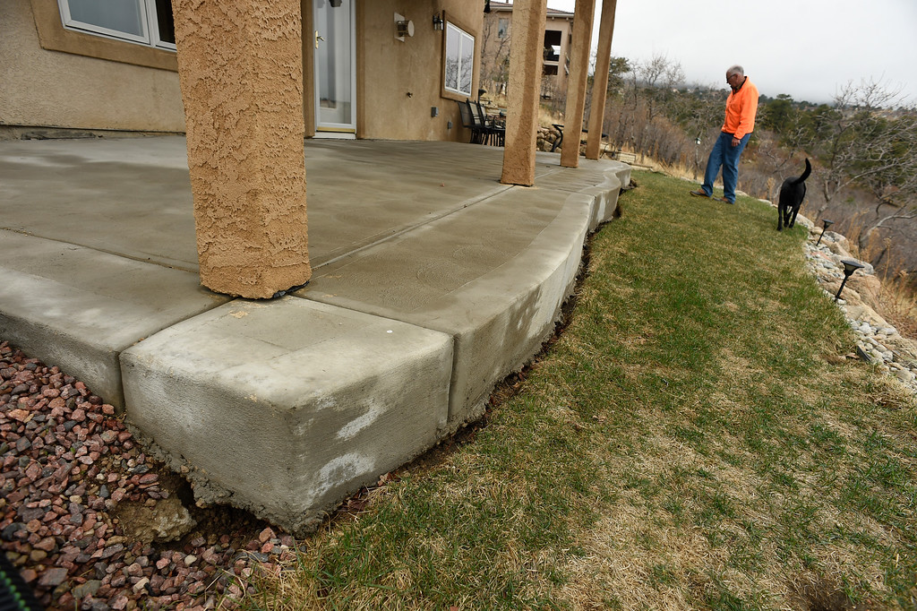 . Homeowner Denny  Cripps checks out the ever increasing crack along the foundation of his house in Broadmoor Bluffs on April 11, 2016 in Colorado Springs, Colorado.  The Cripps are among 200 homeowners who have applied for federal bailouts because their home is being eaten up by collapsing expansive soil that is part of an ancient and massive landslide area.  Their home has cracked walls, uneven floors and is literally sliding down the mountain.  It is a problem that city officials have known about since the mid-1990\'s when city planners approved developments on what geologists have called some of the most unstable geology on the front range.  (Photo by Helen H. Richardson/The Denver Post)