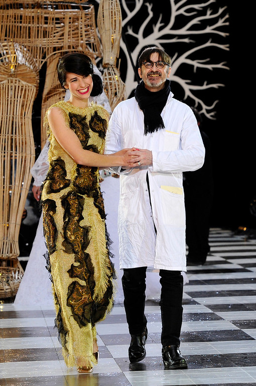 . Fashion designer Franck Sorbier, right, and an unidentified person, acknowledge applause following his Spring-Summer 2014 Haute Couture fashion collection, presented Wednesday, Jan. 22, 2014 in Paris. (AP Photo/Zacharie Scheurer)