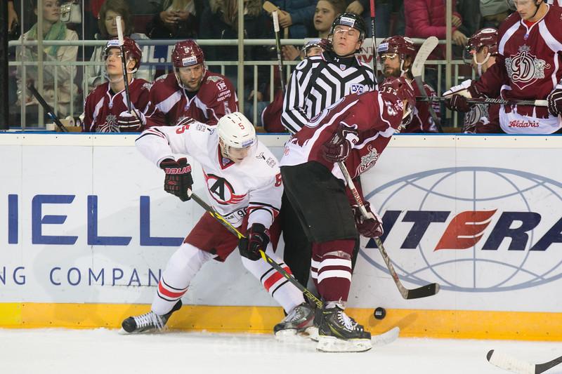 Gunars Skvorcovs (13) of Dinamo Riga tries to protect the puck from Yegor Zhuravlyov (5)