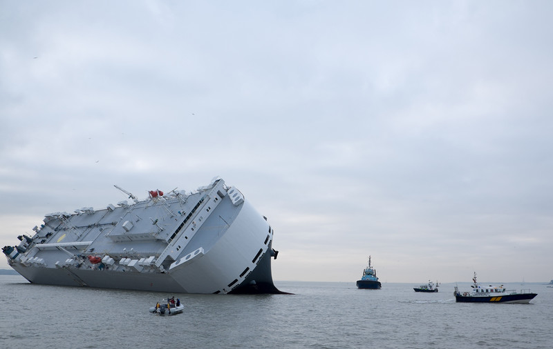 . Small boats sail round the Hoegh Osaka car transporter cargo ship that ran aground in the Solent, off the Isle of Wight Sunday Jan. 4, 2015. The crew members of the Hoegh Osaka were taken to safety by a coastguard helicopter and lifeboats after it became stranded on Bramble Bank, in the Solent between Southampton and the Isle of Wight. (AP Photo/ Francis Bigg Photography)