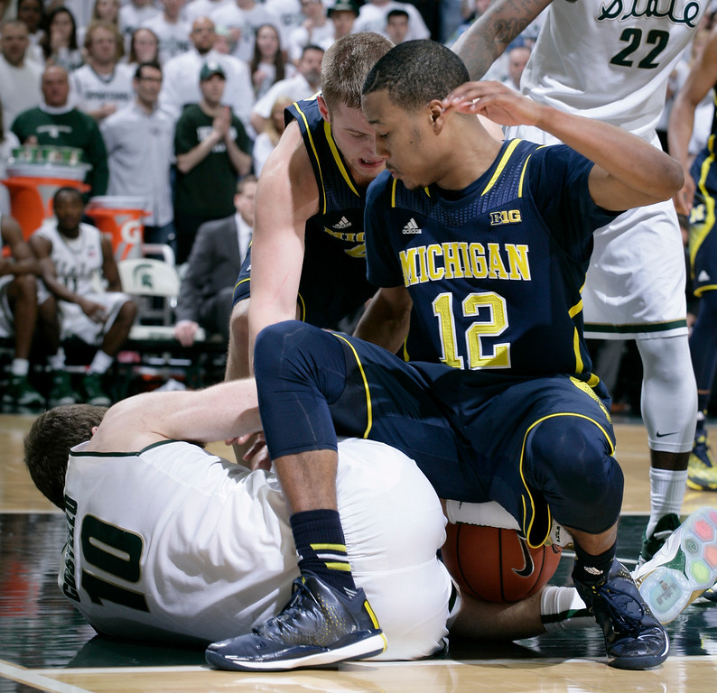 . Michigan State\'s Matt Costello (10), Michigan\'s Muhammad-Ali Abdur-Rahkman (12) and Michigan\'s Max Bielfeldt, rear, wrestle for the ball during overtime of an NCAA college basketball game, Sunday, Feb. 1, 2015, in East Lansing, Mich. Michigan State won 76-66 in overtime. (AP Photo/Al Goldis)