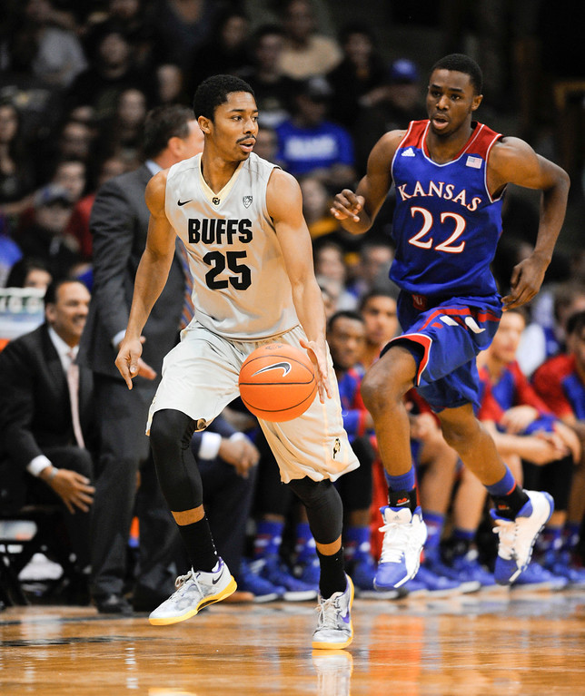 . Colorado University point guard, Spencer Dinwiddie, left, drives up court against Kansas guard, Andrew Wiggins, during the second half of play at the Coors Events Center in Boulder Colorado Saturday afternoon, December 07, 2013. (Photo By Andy Cross/The Denver Post)