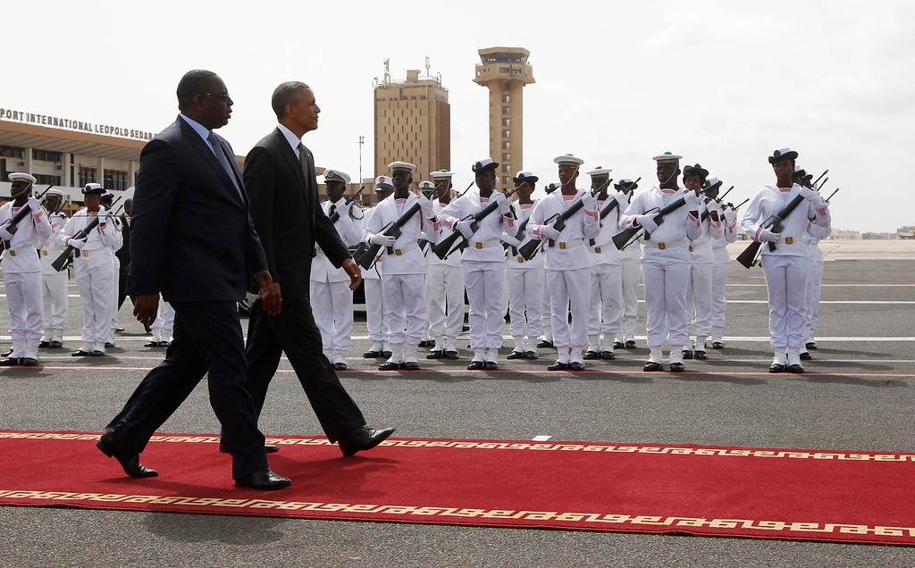 . U.S. President Barack Obama  walks with Senegal\'s President Macky Sall to Air Force One, as Obama departs Dakar, June 28, 2013. Obama heads to South Africa on Friday hoping to see ailing icon Nelson Mandela, after wrapping up a visit to Senegal that focused on improving food security and promoting democratic institutions.  REUTERS/Jason Reed