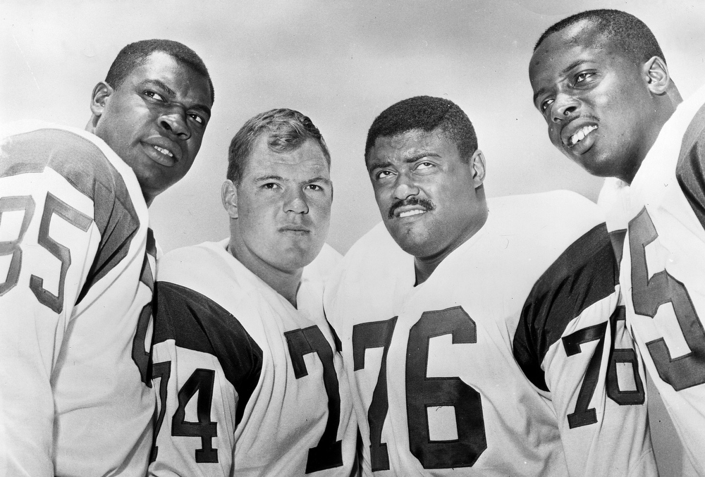 """. This 1964 handout provided by NFL photos,  shows the Los Angeles Rams defensive front four, known as the \""""Fearsome Foursome.\"""" from left to right are Lamar Lundy (85), Merlin Olsen (74), Rosey Grier (76), and Deacon Jones (75). David \""""Deacon\"""" Jones, a Hall of Fame defensive end credited with terming the word sack for how he knocked down quarterbacks, has died. He was 74.  The Washington Redskins said that Jones died Monday night June 3, 2013 of natural causes at his home in Southern California. (AP Photo/NFL Photos)"""