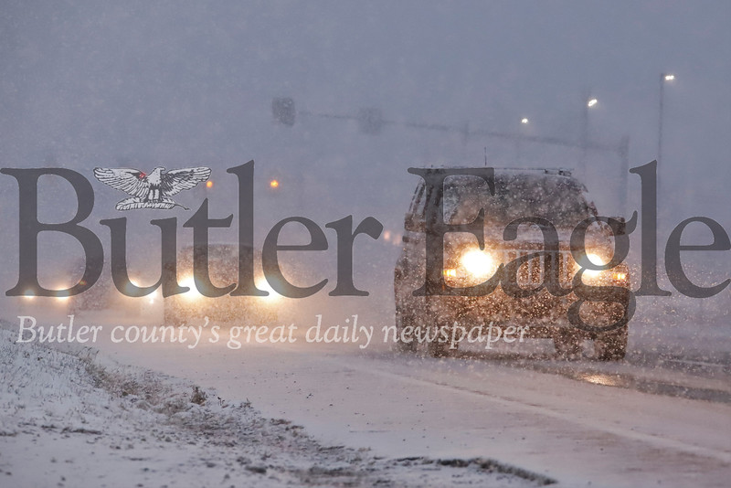Afternoon commuters handle slick roads and near whiteout conditions traveling past the Kelly and Diehl car dealerships on Route 8 south of Butler. Icy conditions plagued rush hour travelers across the county Tuesday evening. Seb Foltz/Butler Eagle