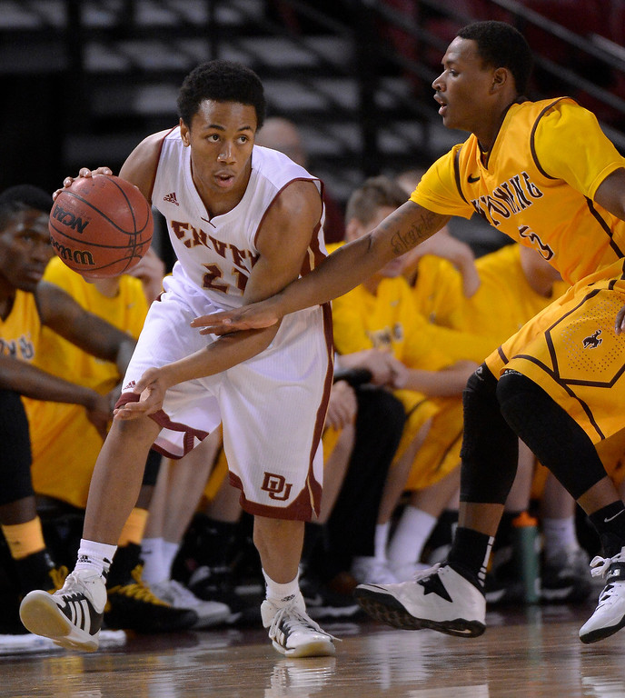 . Denver Pioneers guard Bryant Rucker (21) is guarded by Wyoming Cowboys guard Trey Washington III (5) during he first half December 15, 2013 Magness Arena. (Photo by John Leyba/The Denver Post)